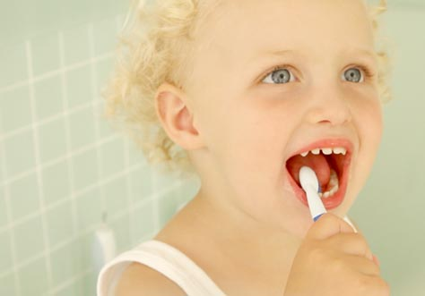 [Translate to Italian:] kid cleaning teeth